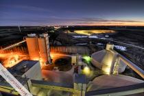 Blick über Milkewerk (Heidelberg Cement) und Steinbruch, der von Baggern beleuchtet wird